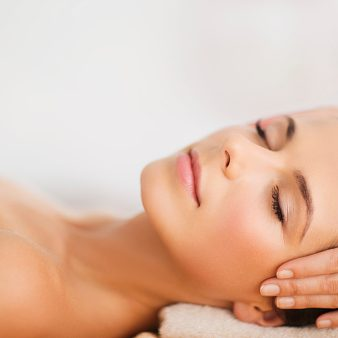 beautiful woman in spa salon having facial